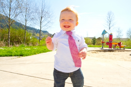 A baby boy plays at the park wearing his Sundays best clothes including a tie around his neck.