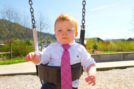 A baby boy plays on a swing set at the park wearing nice clothing. Stock Photo