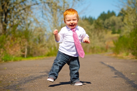 A one year old boy taking some of his first steps outdoors on a path with selective focus while wearing a nice shirt and a necktie.