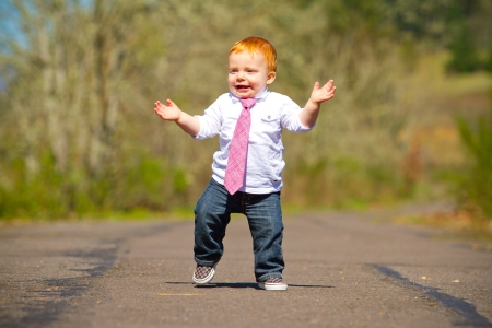 walking baby: A one year old boy taking some of his first steps outdoors on a path with selective focus while wearing a nice shirt and a necktie.