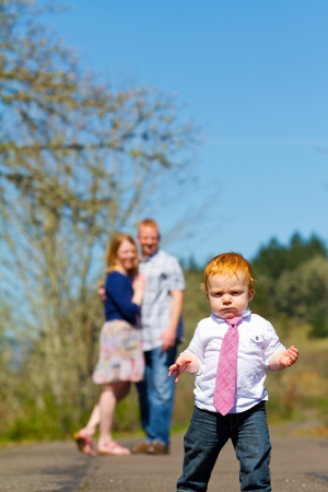 Parents are out of focus in this selective focus image while a baby boy runs toward the camera.