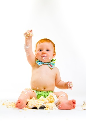 A baby boy gets to eat cake for the first time on his first birthday in this cake smash in studio against a white background.