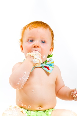 A baby boy gets to eat cake for the first time on his first birthday in this cake smash in studio against a white background. photo
