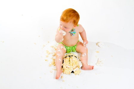 A baby boy gets to eat cake for the first time on his first birthday in this cake smash in studio against a white background. Stock Photo - 20045713