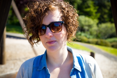 This beautiful attractive woman wears sunglasses outdoors at a park for a simple portrait of a female person. photo
