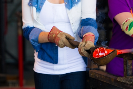 A female is blowing glass and using a wooden shaping tool to form the shape she wants the glass to end up as. The glass is hot and molten so she has to use water with the wood.