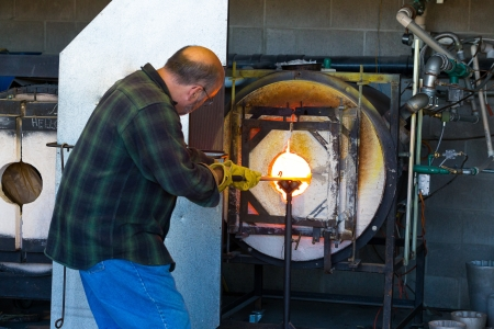 glassblower: A man fires up his glass while glassblowing using a furnace that is extremely hot.