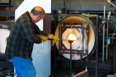 A man fires up his glass while glassblowing using a furnace that is extremely hot.