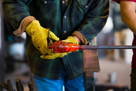 A very talented glassblower is forming and shaping glass in a studio for glass making. He is creating a fluted bowl from this piece of molten glass. Stock Photo
