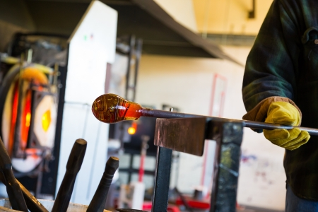 A very talented glassblower is forming and shaping glass in a studio for glass making. He is creating a fluted bowl from this piece of molten glass. Фото со стока