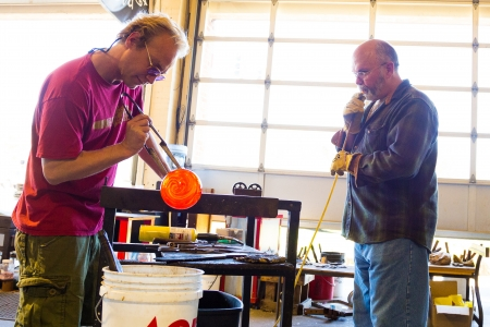 glassblower: Two men are working hard to create a unique art piece of molten glass. They are glassblowing at a studio in Oregon.