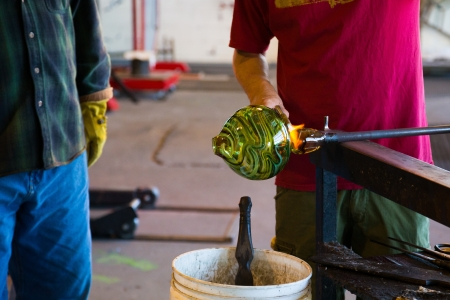 Two men are working hard to create a unique art piece of molten glass. They are glassblowing at a studio in Oregon.