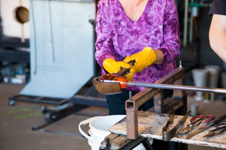 A woman is shaping some motlen glass into a bowl using a wooden forming tool at a glass studio.