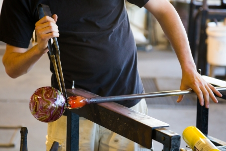 glassblower: A man takes motlen glass and shapes it using some specialized tools for glassblowing art.