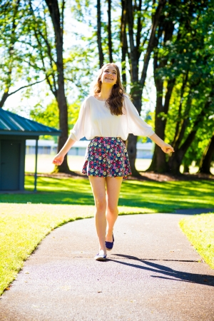 A beautiful young girl poses for a fashion style portrait outdoors at a park with natural lighting.