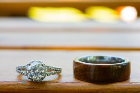 The rings of a bride and groom are photographed on a wooden bench. Imagens