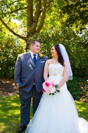 A beautiful bride and groom pose for portraits on their wedding day at a park outdoors. Imagens