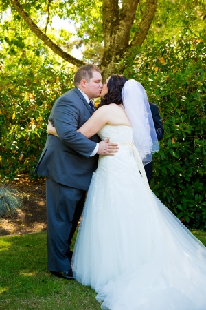 A bride and groom share their first kiss as a married couple and have a moment together during their marriage vows ceremony at an outdoor park in Oregon.