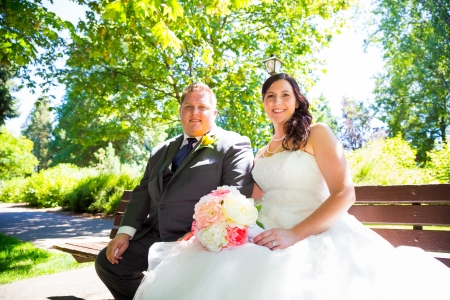 A wedding couple pose for portraits at a park outdoors on their wedding day. The bride and groom are both very happy after just tying the knot and getting hitched.