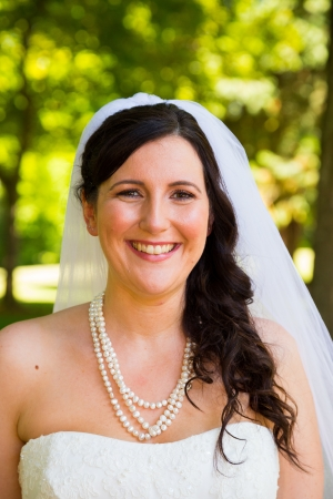 A bride poses for some portraits while wearing her wedding dress at a park outdoors just before here wedding ceremony. Imagens