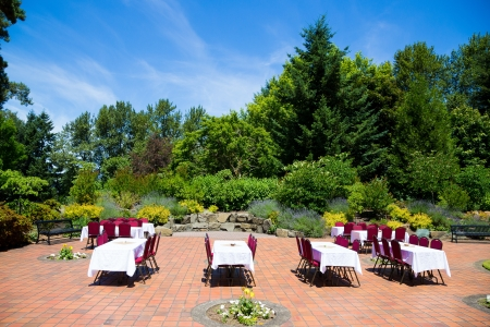 Some tables and chairs are set up ready for a wedding reception as soon the ceremony is finished outdoors in Oregon at a park. The sky is very blue and the patio is surrounded by nature and trees. photo