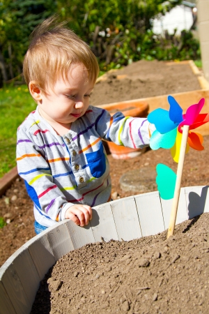 A one year old boy plays with a whirligig propeller pinwheel outside while wearing a striped shirt. photo