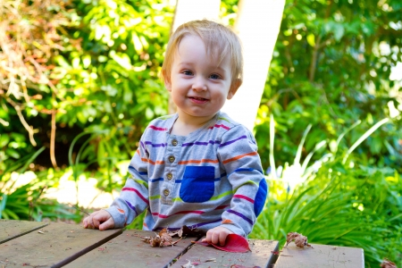 A One Year Old Boy Poses For Picture While Playing With Leaf Outdoors In
