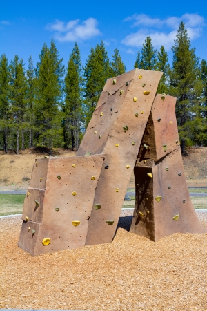 An outdoor rock climbing structure at a playground at a park for kids to practice and play on.