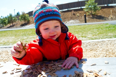 stocking cap: A one-year-old boy plays at a park outdoors with wood chips and structures to keep him entertained. Stock Photo
