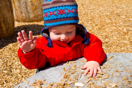 A one-year-old boy plays at a park outdoors with wood chips and structures to keep him entertained. Фото со стока - 21285850