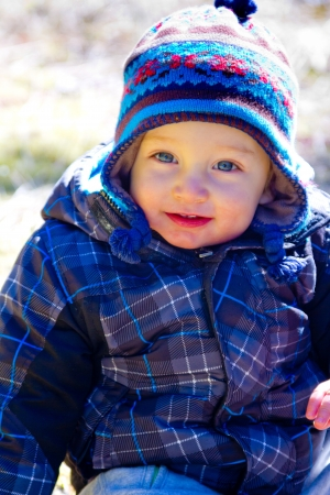 A young boy wears a jacket and warm hat while hiking in the cold near snow in the winter and having fun exploring. Фото со стока - 21285874