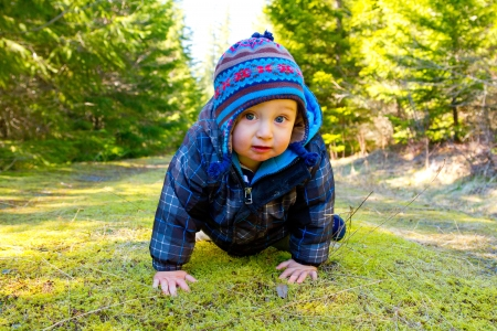 A young boy wears a jacket and warm hat while hiking in the cold near snow in the winter and having fun exploring. photo