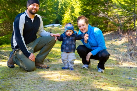 A family of three people stop for a moment to have some photos taken and pose for the camera while hiking in the Oregon wilderness during the spring time. Stock Photo