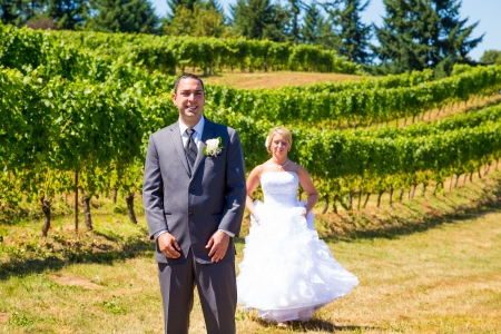 A man and woman share a first look moment as bride and groom outdoors at a winery vineyard in Oregon.