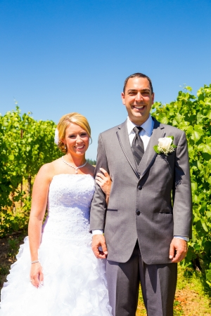 A bride and groom pose for portraits on their wedding day at a winery vineyard outdoors in oregon.