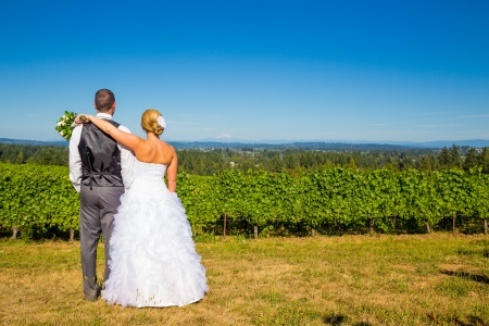 A bride and groom enjoy a view of mount hood in the background from this high elevation winery vineyard in Oregon just outside of Portland.