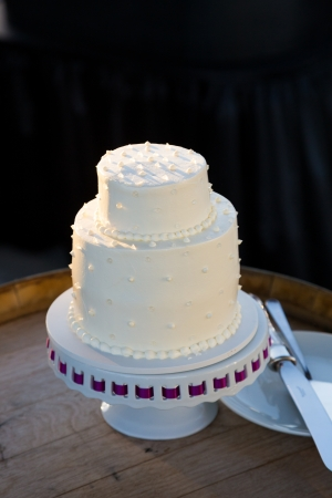 A wedding cake is ready to be cut at a reception on the bride and groom wedding day. photo