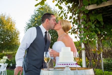 A bride and groom share in the tradition of cutting the cake on their wedding day. Stock Photo