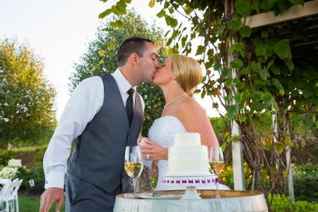 Een bruid en bruidegom delen in de traditie van het snijden van de cake op hun trouwdag.