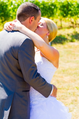 A bride and groom share a romantic kiss on their wedding day at a winery vineyard in oregon.
