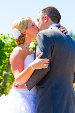 smooch: A bride and groom share a romantic kiss on their wedding day at a winery vineyard in oregon.