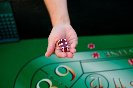 A groom holds dice above a craps table at his casino themed wedding reception. Stock Photo