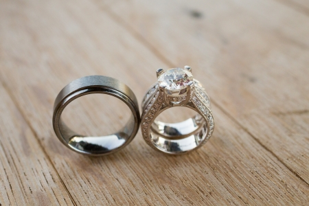 The rings of a bride and groom are photographed with a macro lens to show the closeup detail of these fine pieces of jewelry.