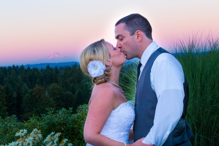 mount hood: A bride and groom kiss during sunset with Mount Hood in the background at their wedding.