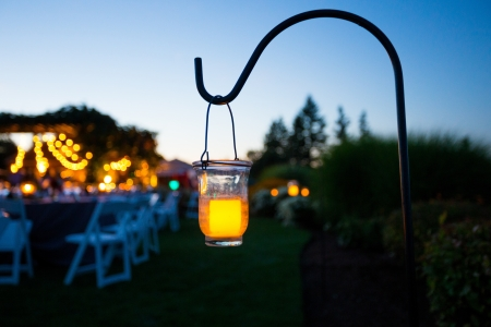 A candle lights up some space at a wedding reception at dusk.