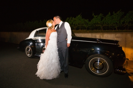 receptions: A bride and groom pose for a last photo in front of an old classic car at a vineyard at night.