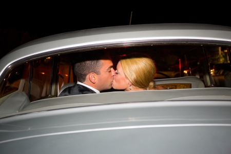 A bride and groom share a last kiss on their wedding day before leaving the reception in a classic old car at night.