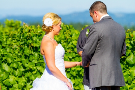 A groom places a ring on the finger of his bride during their wedding ceremony at a winery vineyard in Oregon.