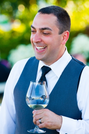 A groom reacts and enjoys the moment during the best man and maid of honor toasts at his wedding. Stock Photo