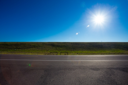 brightness: The bright sun in the blue sky causes this great sun flare along a dam and a road for a unique abstract nature sky landscape in color. Stock Photo